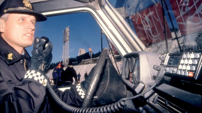 Politiførstebetjent Jan W. Klüver, sambandsavdelingen, benytter Orion radio under OL-94. I bakgrunnen ser vi den olympiske ild og Lysgårdsbakken. Foto: Ericsson A/S.